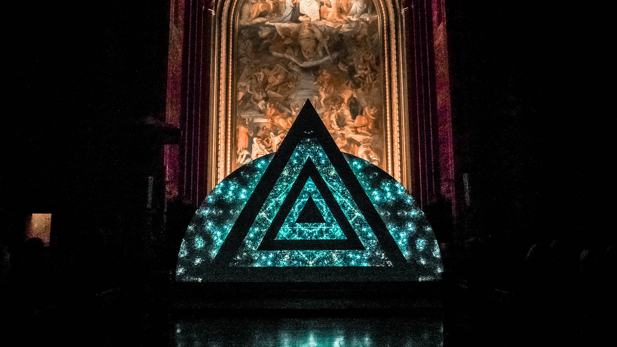 Image of a video art installation. Triangle with geometric and ornamental design. Light art show in a church