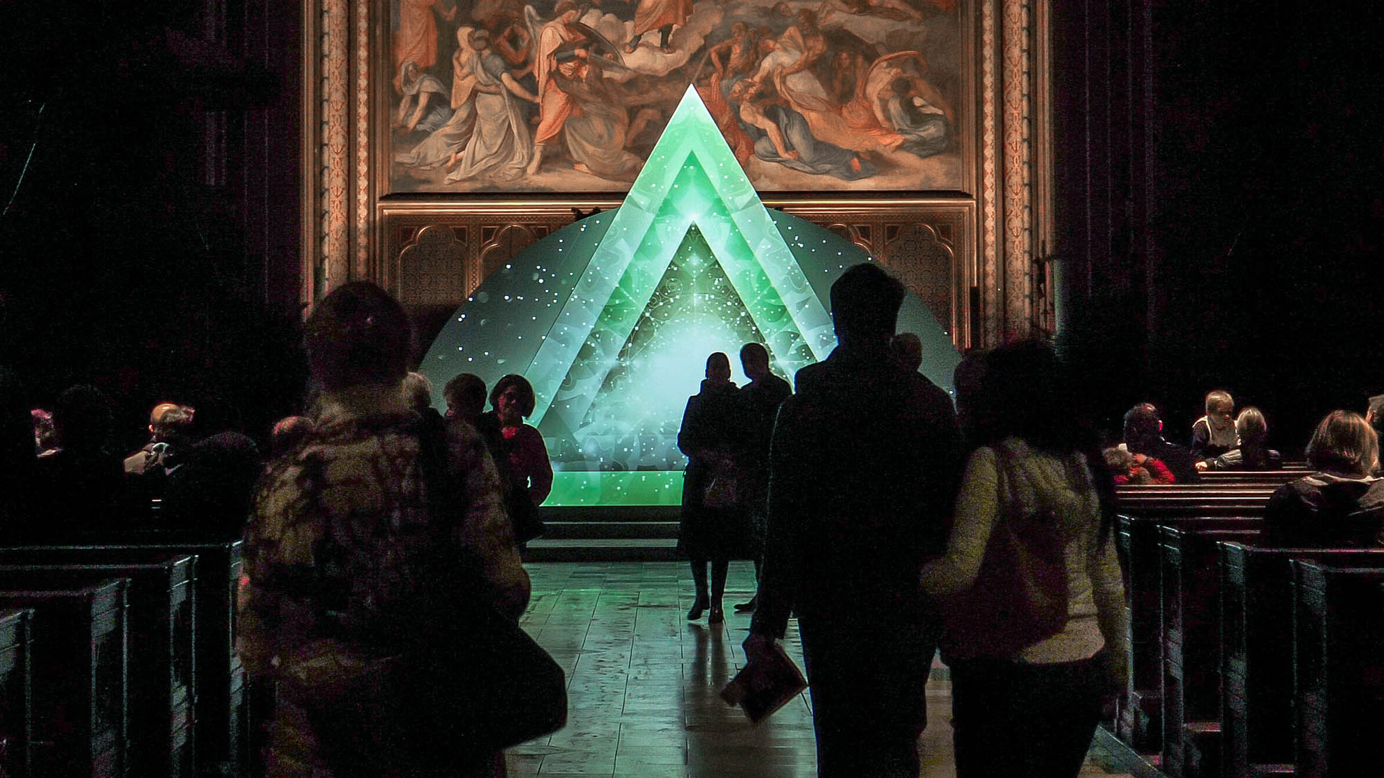 Image of a video art installation in a church with people. Triangle with geometric and ornamental design. Light art show in a church