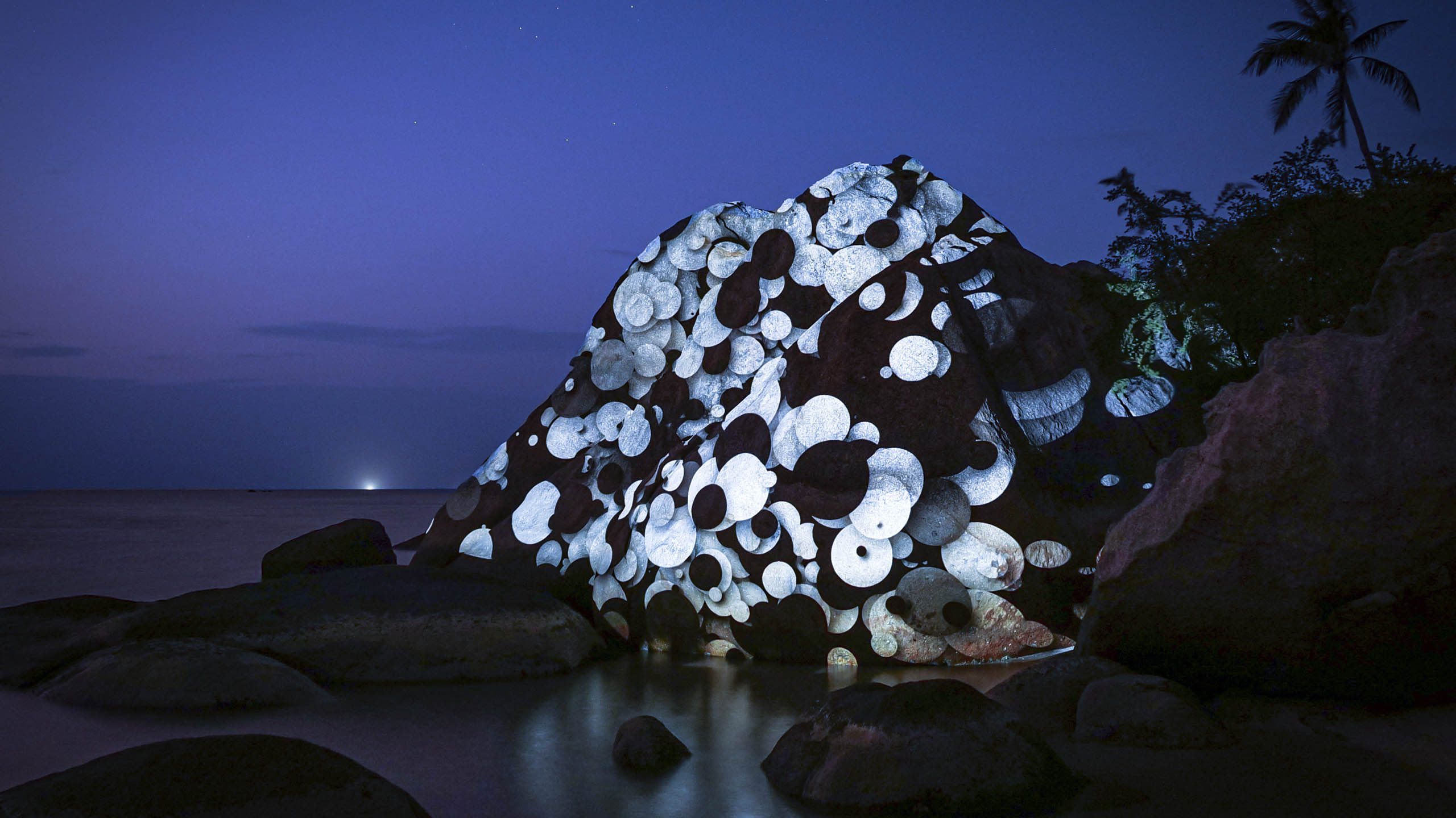 light art, 3d projection mapping with white dots by philipp frank. Located on a rock at the beach