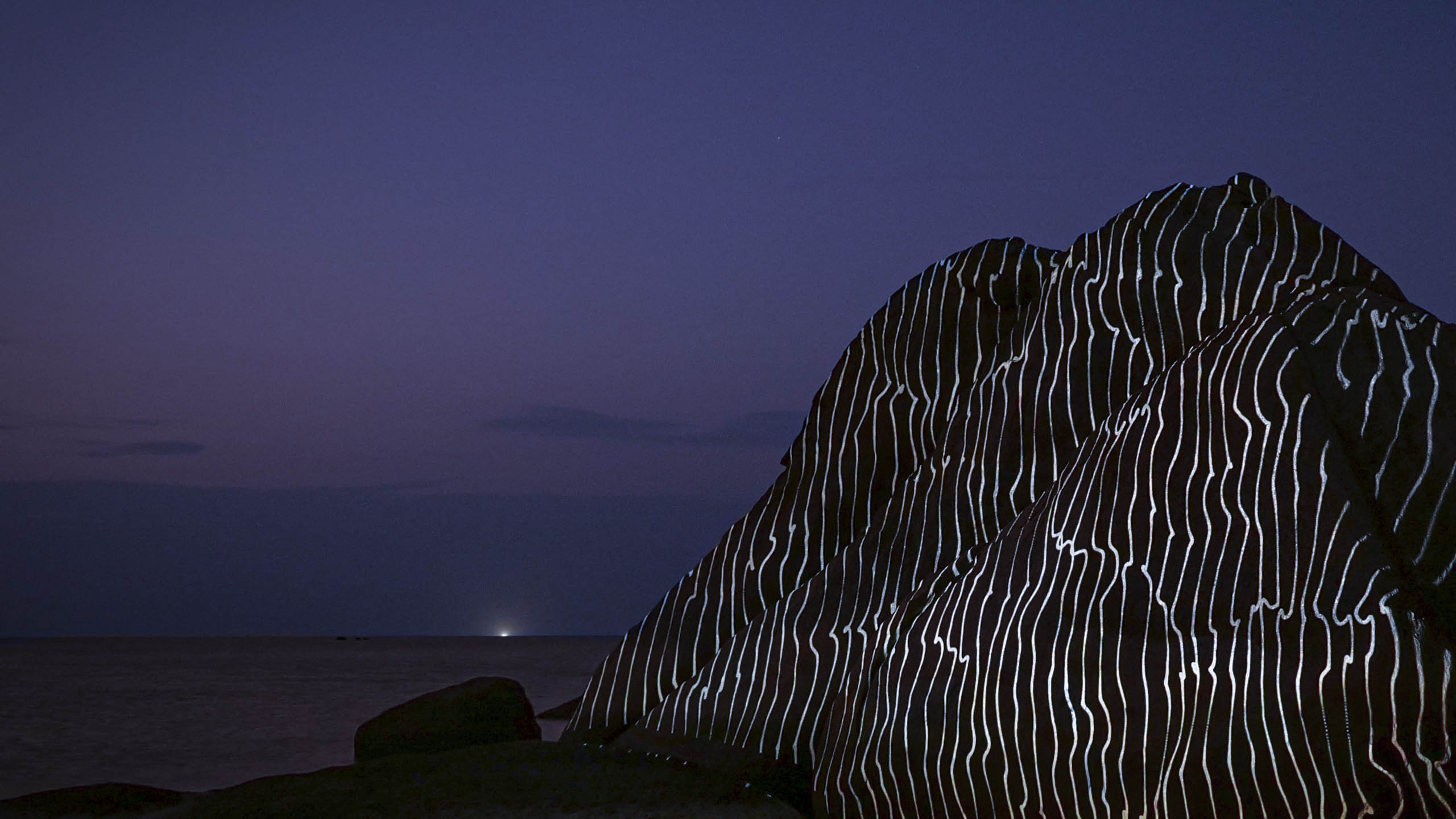 abstract light art, 3d projection mapping with graphic lines by philipp frank. Located on a rock at the beach
