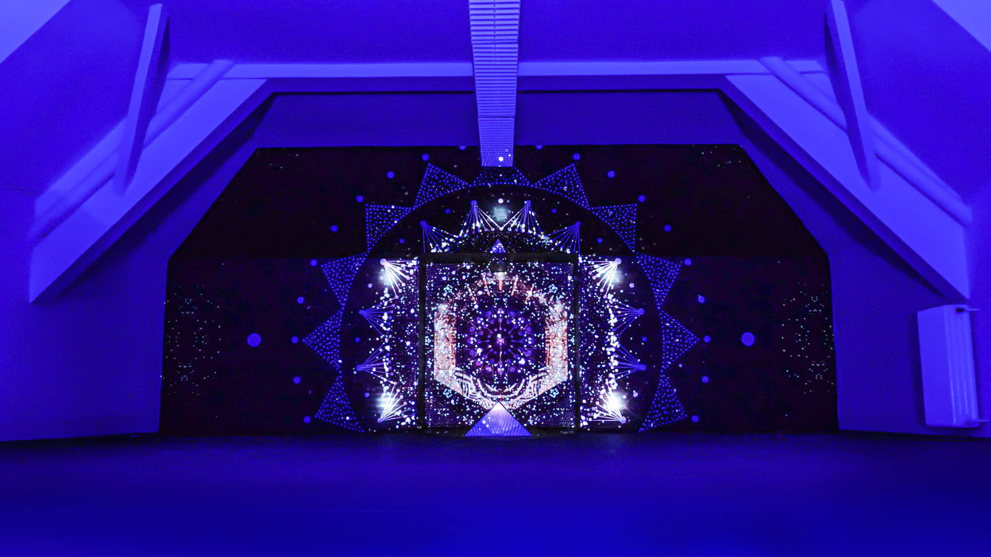 Image of a video art installation combined with a mural painting. Mandala geometric design with projection mapping art.