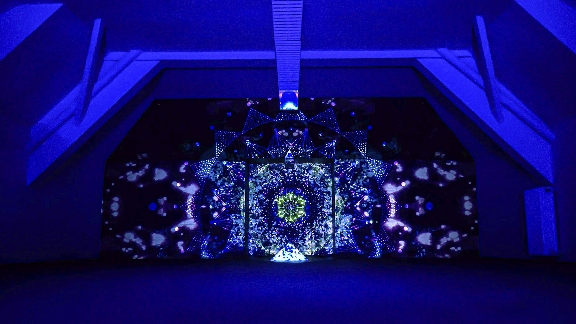 Image of a video art installation combined with a mural painting. Mandala geometric design with projection mapping art. Light artist philipp frank
